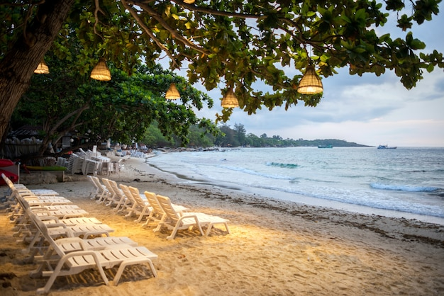 De stoelen met lamp op een boom zijn voorgrond op het strand in samet-eiland in de ochtend, koh samet thailand.