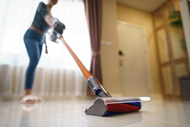 De stofzuiger van het vrouwengebruik het schoonmaken op vloer.