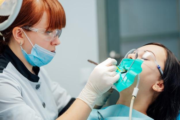 De stomatoloog gebruikt medische instrumenten en behandelt een vrouwelijke patiënt in een veiligheidsbril.