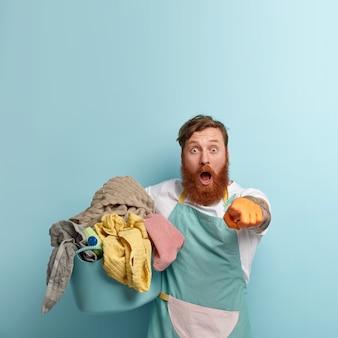De stomverbaasde huishoudster wijst verrassend naar de camera, draagt een blauw schort, houdt een wasbak vast, kan zijn ogen niet geloven