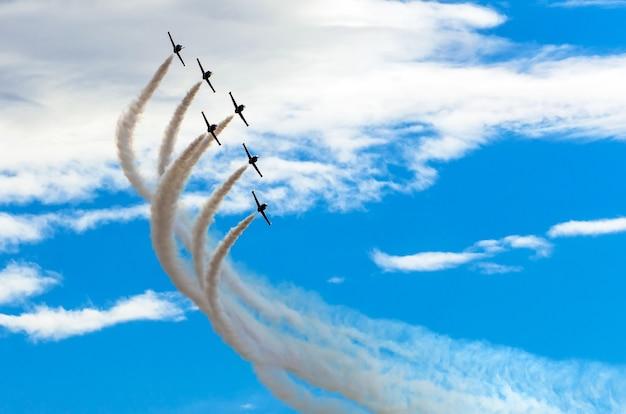De straaljagers van vliegtuigen roken de achtergrond van blauwe hemel witte wolken