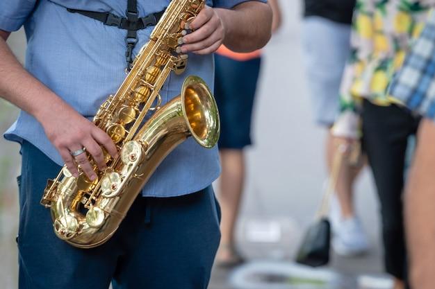 De straatmuzikant die saxofoon speelt.
