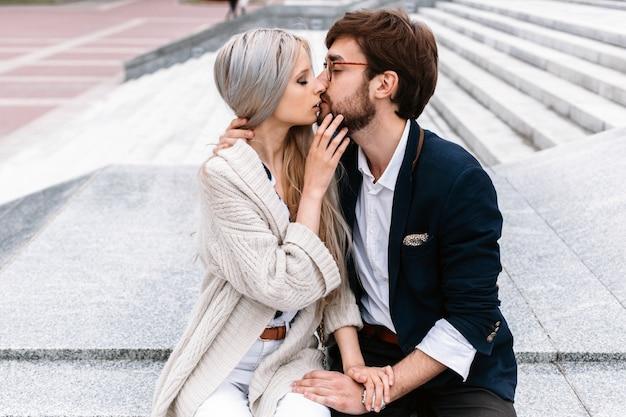 De straatportret van de close-upzomer van het mooie modieuze manierpaar openlucht kussen