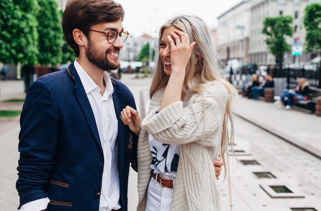 De straatportret van de close-upzomer van mooi modieus manierpaar die en pret lachen hebben openlucht