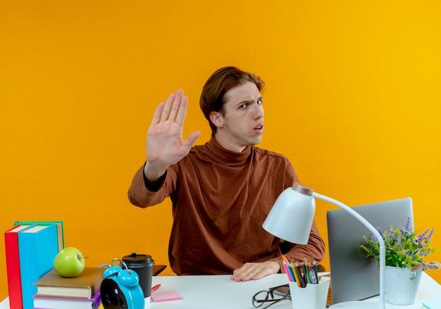 De strikte jonge zitting van de studentenjongen aan bureau met schoolhulpmiddelen die stopgebaar op geel tonen