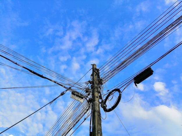 De stroompaal met veel draden eraan verbonden vanuit lage hoekmening met blauwe lucht