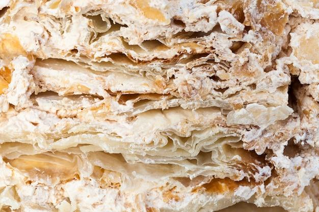 De structuur van een gesneden cake met een gelaagde structuur met een crème van bruine kleur, in stukken verdeeld tijdens de viering van de bruiloft
