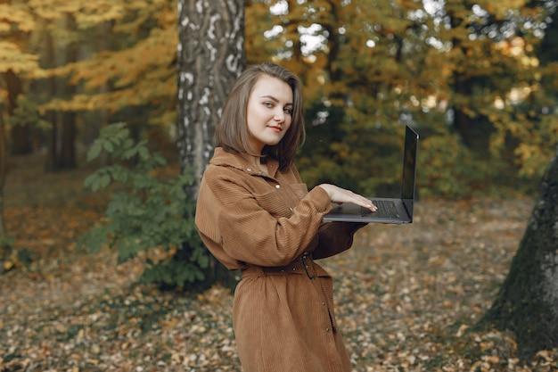 De student die in een park werkt en gebruikt laptop