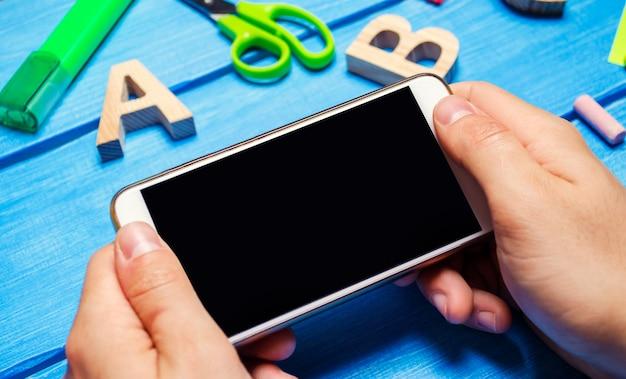 De student houdt een mobiele telefoon op de achtergrond van een creatieve puinhoop op het bureaublad