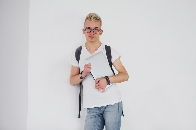 De student in vrijetijdskleding en met rugzak bevindt zich binnen tegen witte muur met laptop
