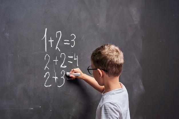 De student lost een rekenvoorbeeld op een schoolbord op