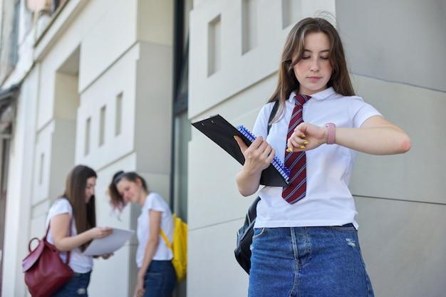De studente bekijkt polshorloge, universiteitsonderwijs, openlucht tienersstudenten