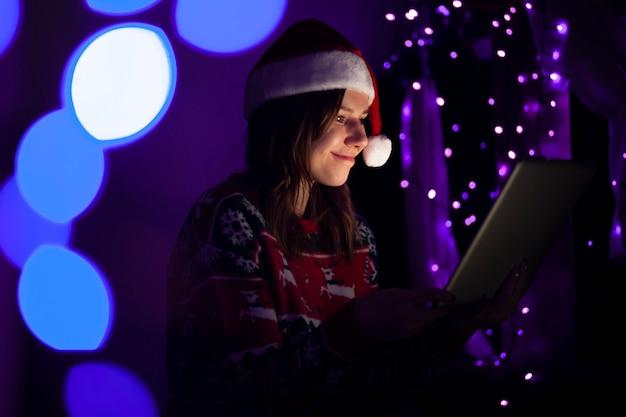 De studente in kerstmiskleren zit thuis met laptop bij nacht