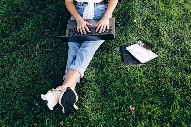 De studente met laptop zit buiten op het gras in het park