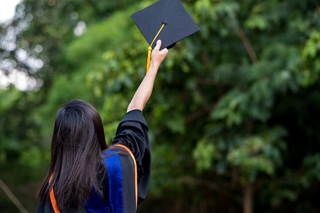De studenten die een schot van afstudeerpet houden tijdens ceremoniesucces afgestudeerden aan de universiteit