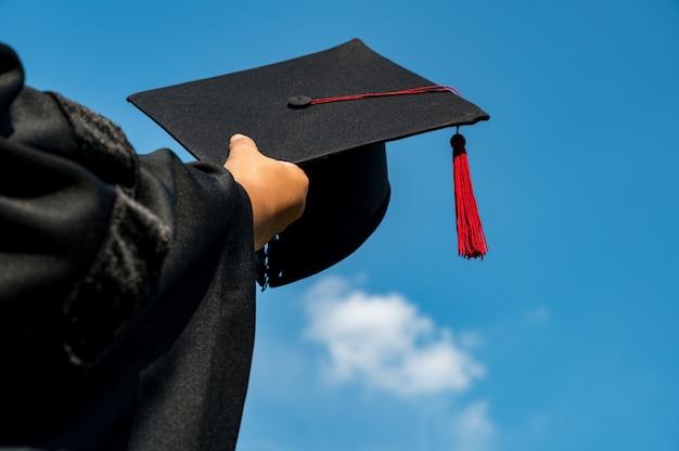 De studenten houden een schot van afstuderen cap door hun hand in een heldere hemel