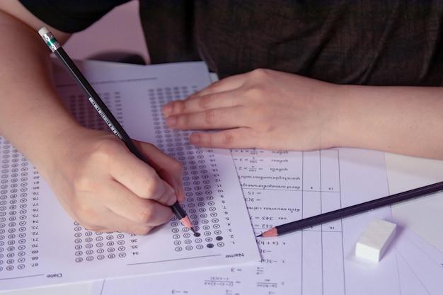 De studenten overhandigen holdingspotlood die geselecteerde keus schrijven op antwoordbladen en de vraagbladen van de wiskunde. studenten testen doen examen. school examen