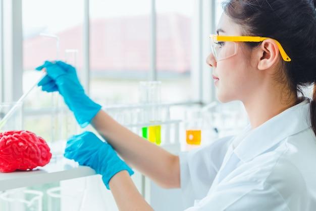 De studentenstudenten die van de close-upwetenschap met chemische producten in laboratorium werken