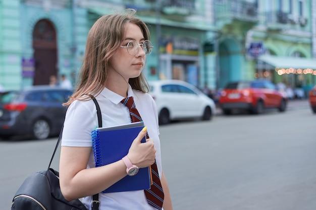 De studententiener van het portretmeisje in glazen binden wit t-shirt met rugzak.