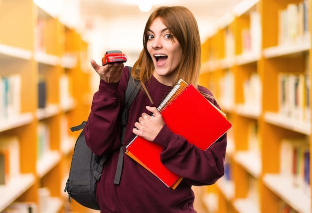 De studentenvrouw die weinig auto houden unfocused achtergrond. terug naar school
