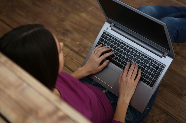 De studentenvrouw houdt laptop op haar knieën zittend op de vloer en leert, met diepte van gebiedsbeeld