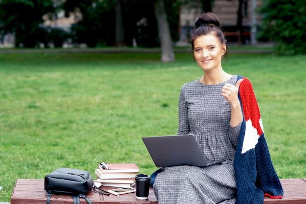 De studentenvrouw met laptop toont duim bij het park.