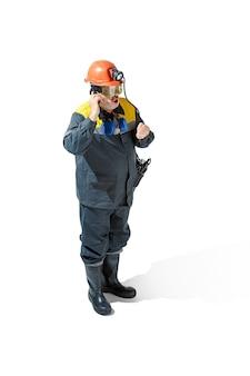 De studio-opname van een senior bebaarde serieuze mannelijke mijnwerker in een professionele helm die voor de camera staat