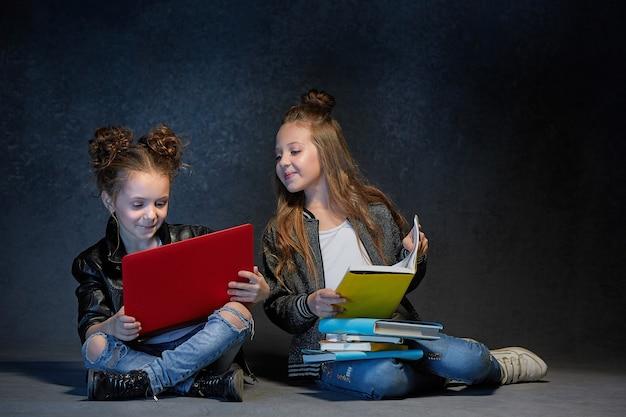 De studio-opname van kinderen met boek en laptop