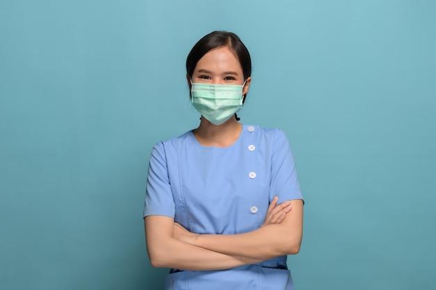 De studiofoto van het portret van jonge aziatische verpleegster die gezichtsmasker op blauw draagt.