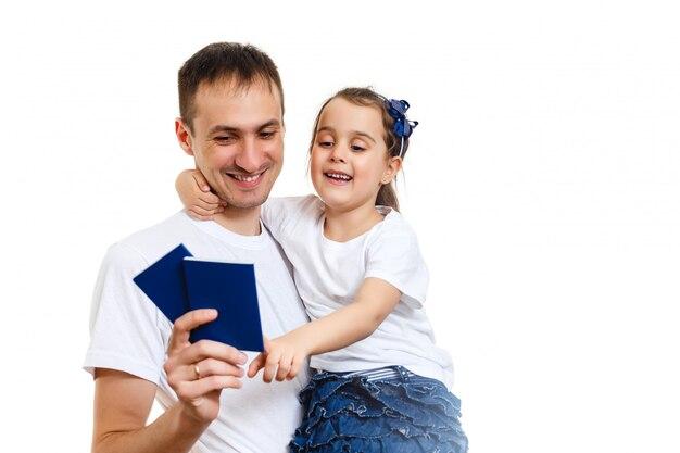De studioportret van het reisconcept van vrij jonge papa met handen die paspoort met kaartjes tegenhouden