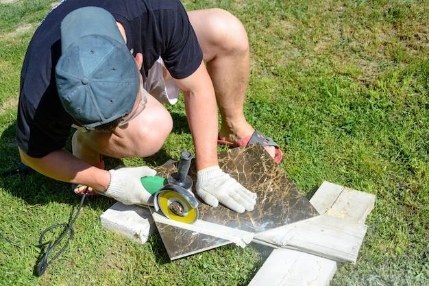 De stukadoorsmeester snijdt de marmeren tegel rond de keramische schijf