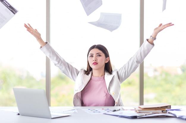 De succesmanager, bedrijfsvrouw werpt werkend document in bureau met laptop