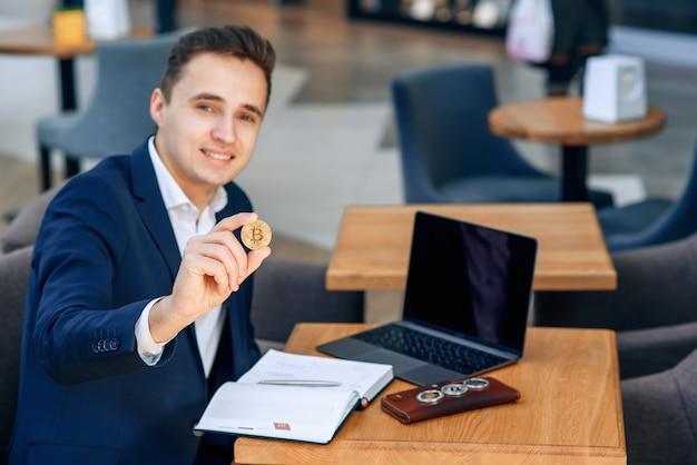 De succesvolle glimlachende zakenman houdt een gouden bitcoinmuntstuk in zijn hand