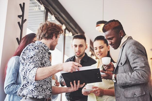 De succesvolle jonge bedrijfsmensen spreken en glimlachen tijdens de koffiepauze in bureau