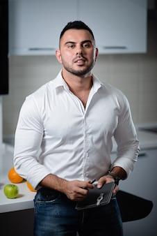 De succesvolle mens in een wit overhemd met een notitieboekje in zijn handen bevindt zich dichtbij de lijst