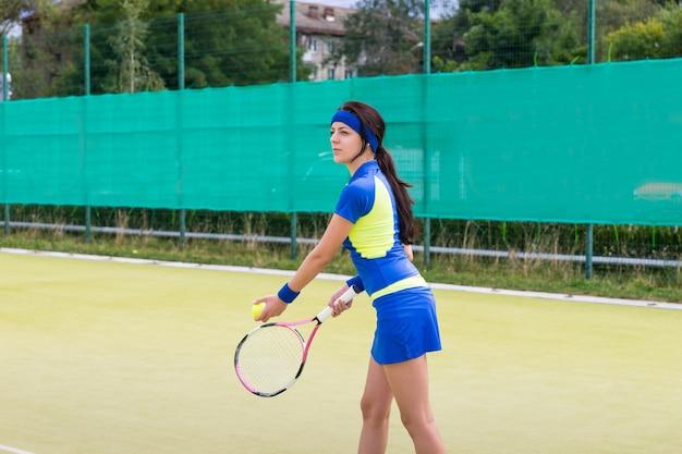 De succesvolle sportvrouw die tenniswear draagt, bereidt zich voor op het spel op een hof buiten in de zomer of de lente