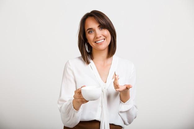 De succesvolle vrouw drinkt koffie en het glimlachen