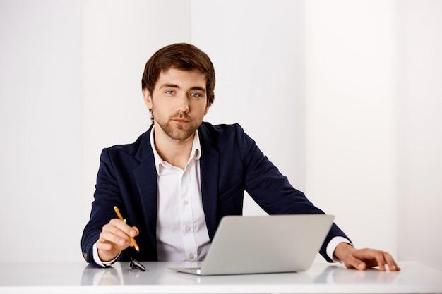 De succesvolle zakenman zit op zijn kantoor, werkend aan project met laptop, houdt potlood en kijkt