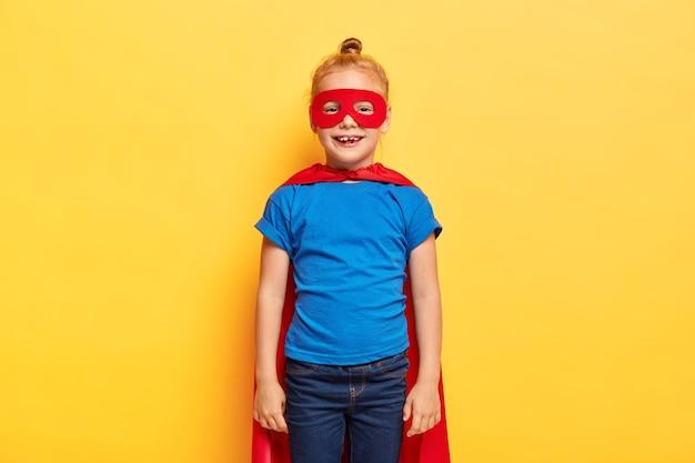 De superheldin van het kleine meisje draagt een speciaal pak met een rode cape