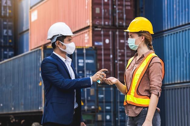 De supervisor die een beschermend chirurgisch masker draagt, staat voor een lichamelijk onderzoek en drukt de alcoholgel op de collega voordat hij de werkplek in de magazijncontainer binnengaat.