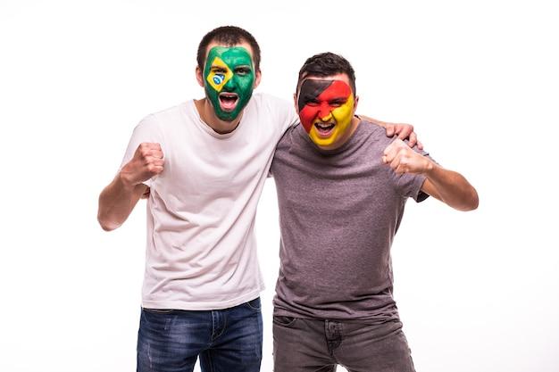 De supporters van voetbalfans met geschilderd gezicht van nationale teams van brazilië en duitsland die op witte achtergrond worden geïsoleerd