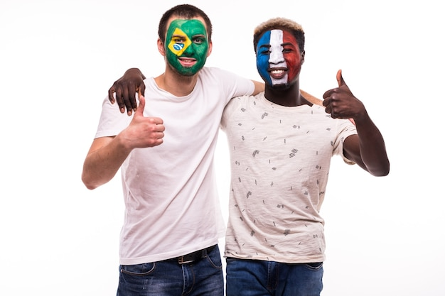 De supporters van voetbalfans met geschilderd gezicht van nationale teams van frankrijk en brazilië die op witte achtergrond worden geïsoleerd