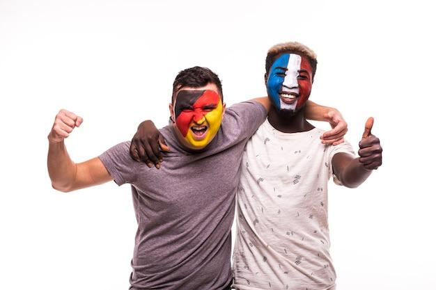 De supporters van voetbalfans met geschilderd gezicht van nationale teams van frankrijk en duitsland die op witte achtergrond worden geïsoleerd