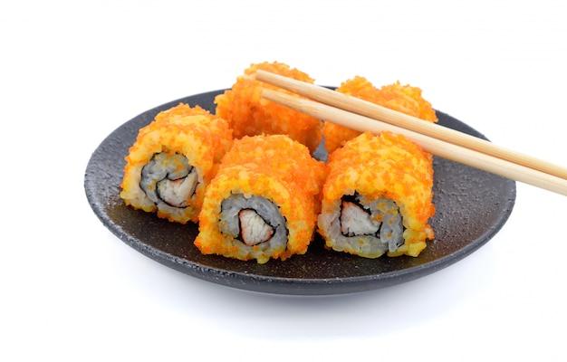 De sushi rolt japans voedsel op zwarte plaats op wit