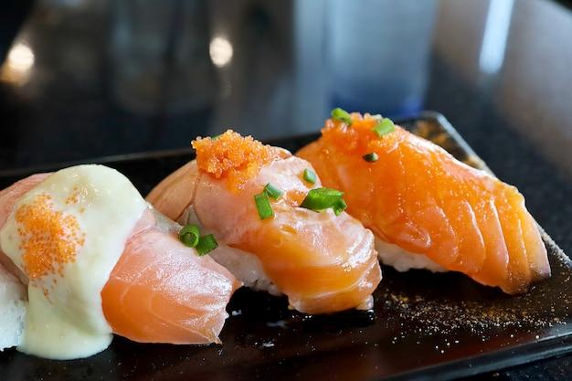 De sushi van de zalm van de close-up in zwarte plaat.