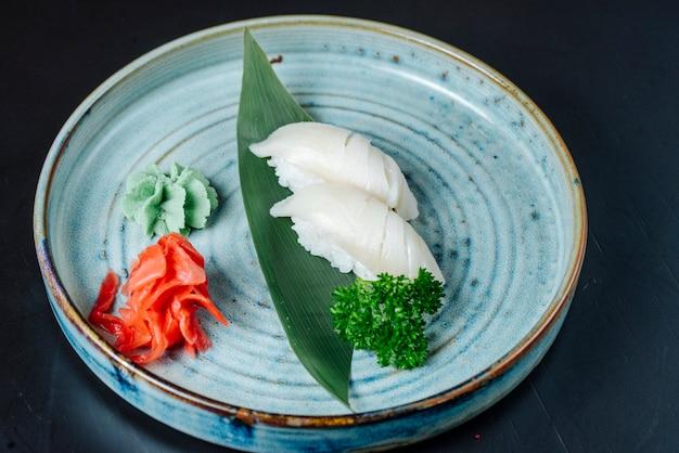 De sushi van vooraanzichtsashimi met witte vis met wasabi en gember op een plaat
