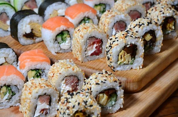 De sushireeks van een aantal broodjes wordt gevestigd op een houten scherpe raad op een lijst in de keuken van een sushistaaf
