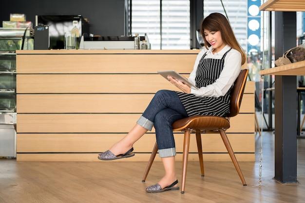 De tablet van de bedrijfseigenaarholding zit op stoel voor de koffiewinkel met een kmio