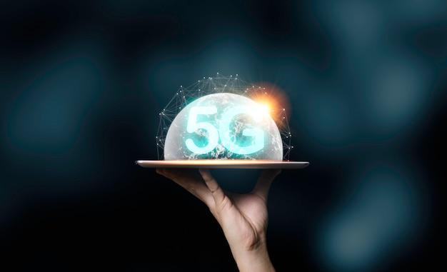 De tablet van de handholding met 5g-verwoording en virtuele wereldillustratie. technologie transformatie concept.