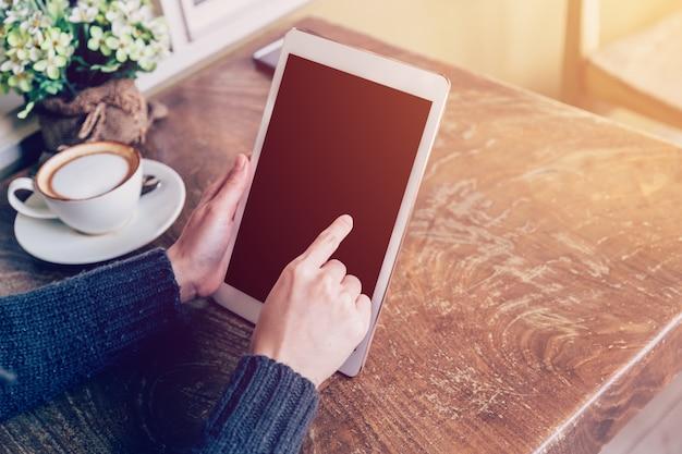 De tablet van de handvrouw het spelen in koffiewinkel met uitstekende toon.